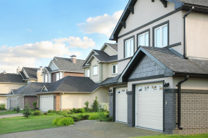 Street with two-storied brown cottages with built-in garage and green grass near houses - Let Precision inspection inspects your home.