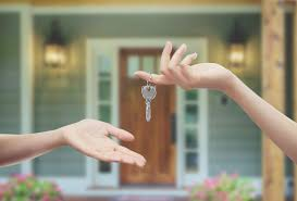 A person giving a key to new home owners - Precision Inspection, your Southern Home Inspection company will inspect your home first before buying it.